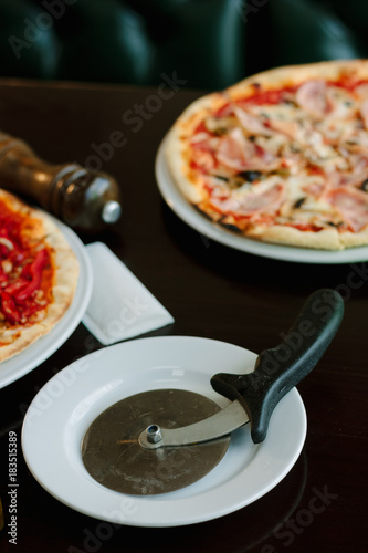 Pizza cutter on white plate Poster