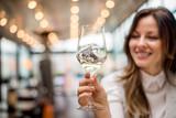 Closeup of woman holding glass of wine in cafe restaurant. - 183522181