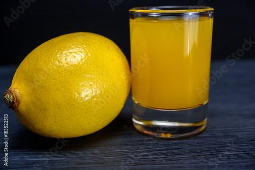 Poster Lemon and lemon juice on a dark wooden background