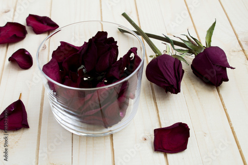 Dried rose petals in the glass on the light wooden background