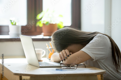 Tired young woman falling asleep at desk after overwork. Exhausted sleep deprived stressed female manager lying on table and sleeping after hard working day, no energy left