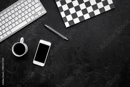 Concept of the strict office desk in monochrome. Keyboard, notebook, cell phone,  coffee on black background top view copyspace