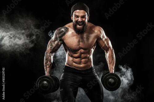 Sticker Muscular young fitness sports man workout with dumbbell in fitness gym
