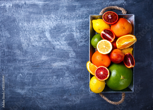 Different Citrus Fruit on a Blue Background .Mixed Colorful Tropical Background.Food or Healthy diet concept.Vegetarian.Toned image.Copy space for Text. selective focus.