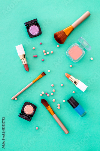 Set of decorative cosmetics. Lipstick, eye shadows, nail polish, rouge, brushes for makeup on blue background top view