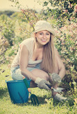 positive young woman working in garden among green plants and flowers - 183537769