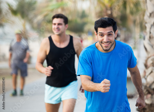 Fotobehang Hardlopen Portrait of adult man who is jogging with friend