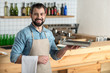 Smiling waiter. Positive friendly bearded waiter feeling glad while being at work and standing next to a bar counter with a nice tray in his hand