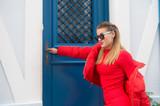 Woman in red sweater, coat at blue door in paris