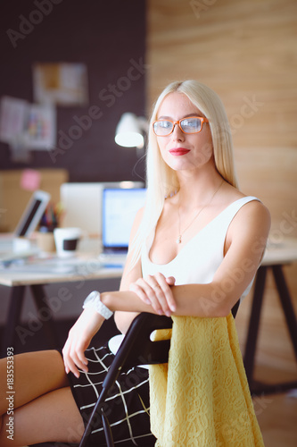 Wall mural Portrait of an executive professional mature businesswoman sitting on office desk