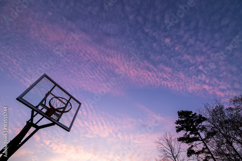 Obraz na płótnie Silhouette of outdoor basketball goal with clear backboard and sunset in the background