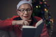 Senior old lady reading her favorite book during December holiday, house decorated with a christmas tree, she's wearing a christmas hat