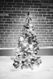 monochrome Christmas tree with festive lights in snow outdoors, brick wall background - 183558316