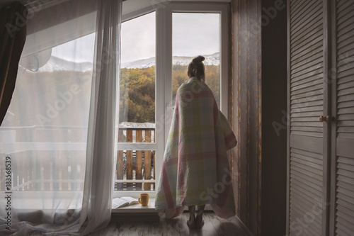 Girl stands near the window with mountain view in hotel room at morning time.