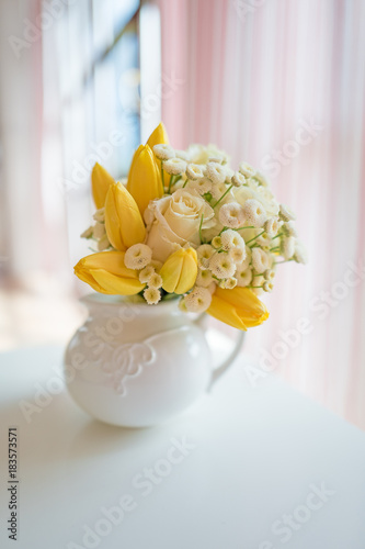 Romantic bouquet of yellow tulips and white roses in white porcelain jug