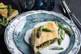 Grüner Spargel im Teigmantel auf einem Teller mit Hollondaise - 183575539