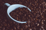 White Cup drowned in coffee beans, toned photo - 183578154