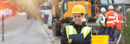 panoramic view of young female architect with construction team