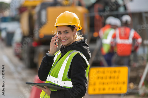 Fototapeta female construction woman using electronics on construction site