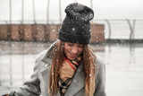 Portrait of a girl in a hat and a gray coat. A young woman is walking in the snow in the city.