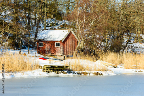 Red Wooden Boatshed In Winter Landscape Pier And Reed At Shoreline Woodland