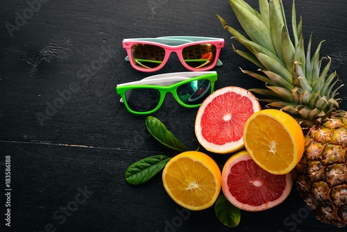 Pineapple and citrus fruits on a wooden background. Tropical fruits and nuts. Top view. Free space for text.