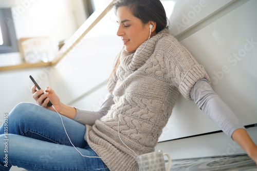 Fotobehang Muziek Woman relaxing at home listening to music with smartphone