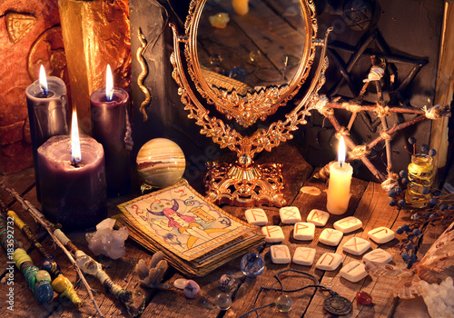 Old books, black candles, mirror, tarot cards and runes on