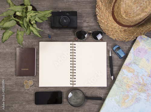 note book and world map for planning vacation with other travel accessories around.