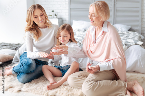 Sticker Staying beautiful. Positive cute delighted girl sitting together with her mother and grandmother and holding a bottle of facial cream while learning how to use it