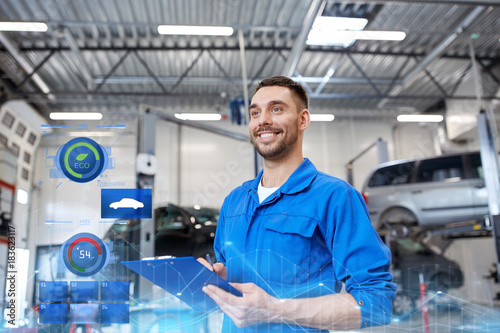 happy mechanic man with clipboard at car workshop