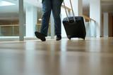 Closeup of traveller pulling suitcase in airport corridor
