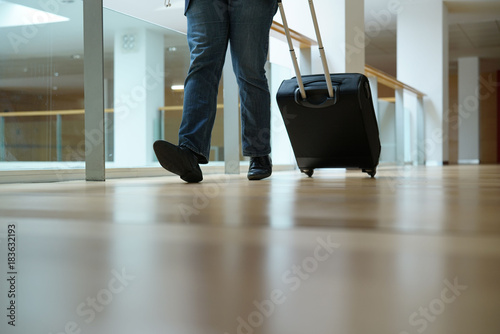Closeup of traveller pulling suitcase in airport corridor - 183632193
