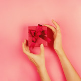 Woman's hands reaching for a present in red box on pink background, romantic flat lay, toned image, square - 183632349