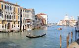a gondola sails along the beautiful Grand canal, the Basilica di Santa Maria della Salute in Venice, Italy
