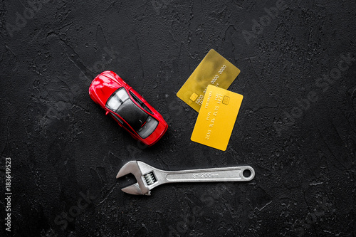 Pay for car repair. Wrench near car toys and bank card on black background top view