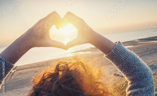 Leinwandbild Motiv Woman hands in Heart symbol shaped with sunset light on the beach, Lifestyle and Feelings concept image