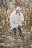 The girl in white furry coat stands in the middle reeds in the winter 9136. - 183651350