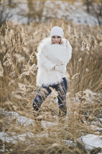 The girl in white furry coat stands in the middle reeds in the winter 9137.