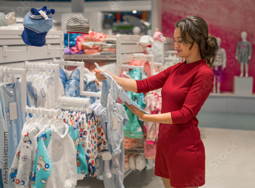 856ad58a5 Customer young woman choosing baby clothes or children s wear in the ...