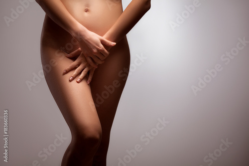 Leinwanddruck Bild Nude woman covering her intimate part of body.