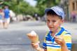 Cute European boy eating ice cream cone in a town street.