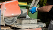 Building contractor working with a concrete block and an angle grinder