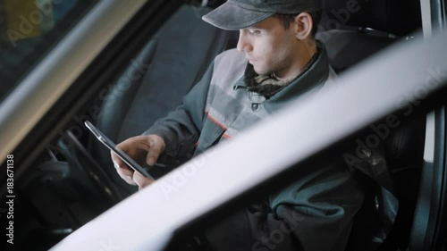 Mechanic sits in a car with a tablet.