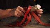 Close-up shot of male hands of craftsman making cylinder wicker case. Handmade things - 183673991