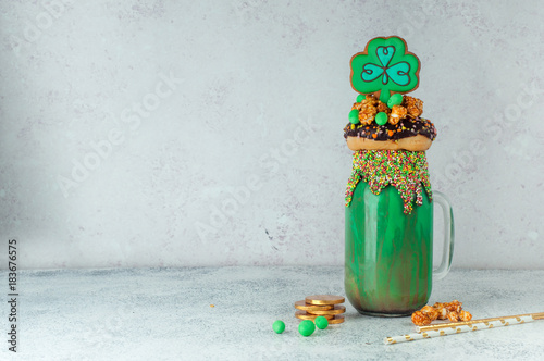 Fotobehang Milkshake St. Patrick's Day green freak shake topping with clover cookie with copy space