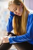 Sad depressed teen girl sitting on window sill - 183680103