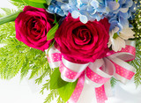 Big red roses and small blue fragile flowers insert leaves in the beautiful flower bouquet - 183687547