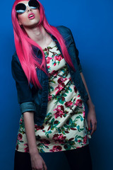 fashion model with pink hair and big sunglasses over blue  background