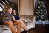 Beautiful young couple in the New Year atmosphere with puppies of the Husky - 183690713